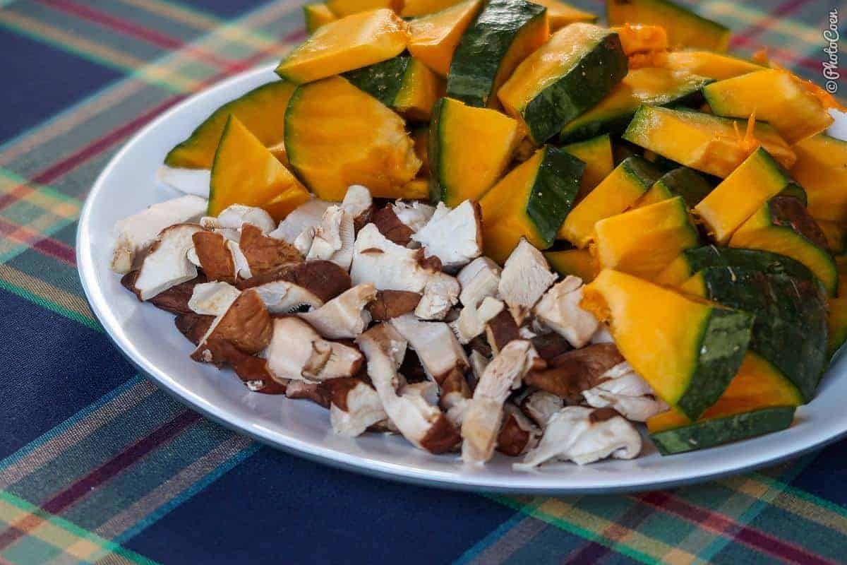 ingredients for pumpkin soup: chunks of pumpkin and mushrooms on a plate.