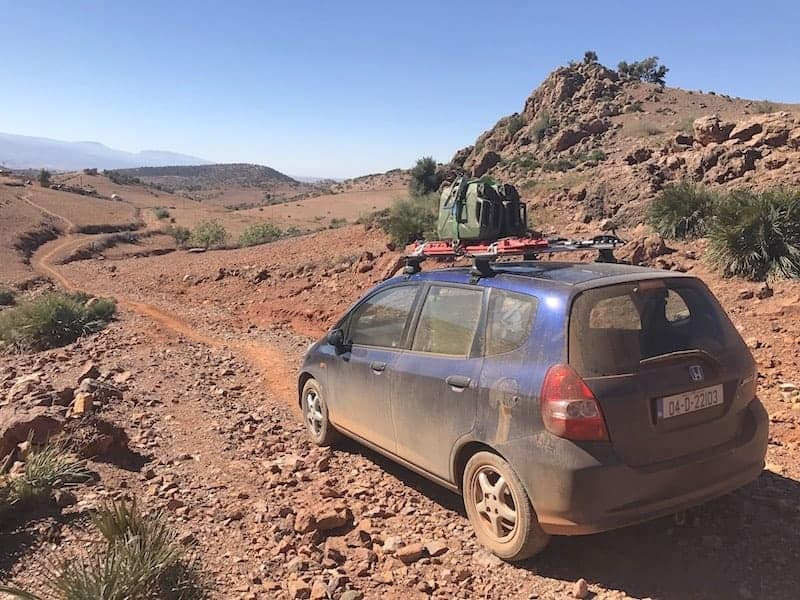 Overland vehicles: a blue Honda Jazz with 2 jerry cans on the roof amidst a red stony desert
