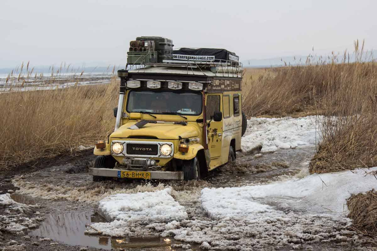 Off-road adventure in Russia - a yellow Land Cruiser plotting through a muddy, icy and snowy trail.