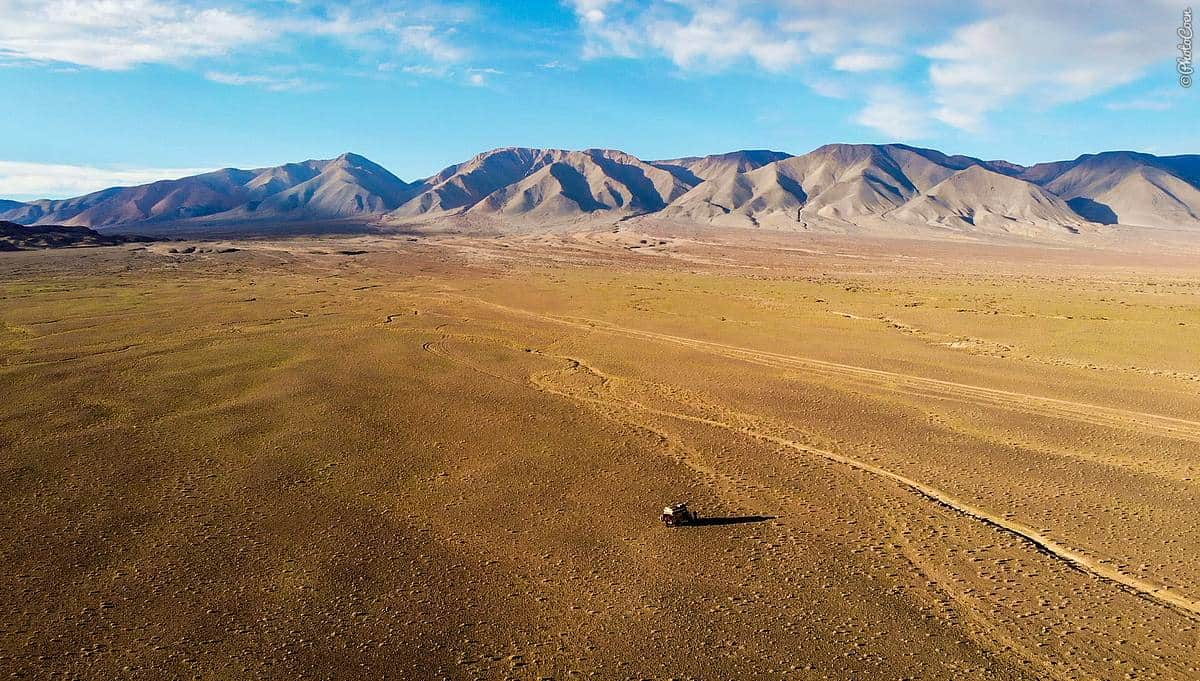 The Gobi Desert - an aerial shot of an empty landscape hemmed in by mountains with the Land Cruiser as a dot in field.