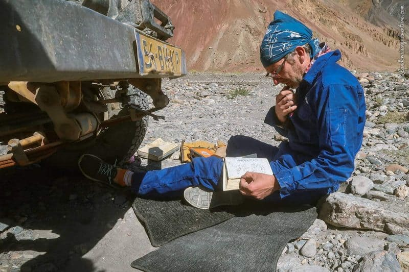 Coen searching in his Toyota workshop book for a solution to fix the broken steering, Bartang Valley, Tajikistan