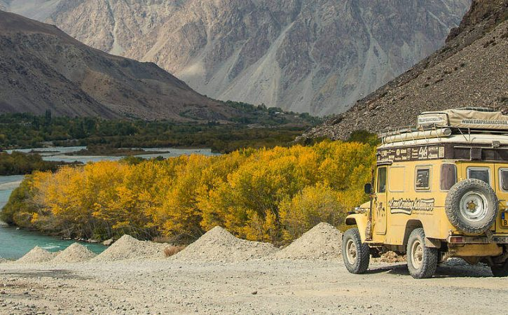 Overland Travel on the Pamir Highway in Tajikistan, mountains, autumn leaves, yellow Land Cruiser