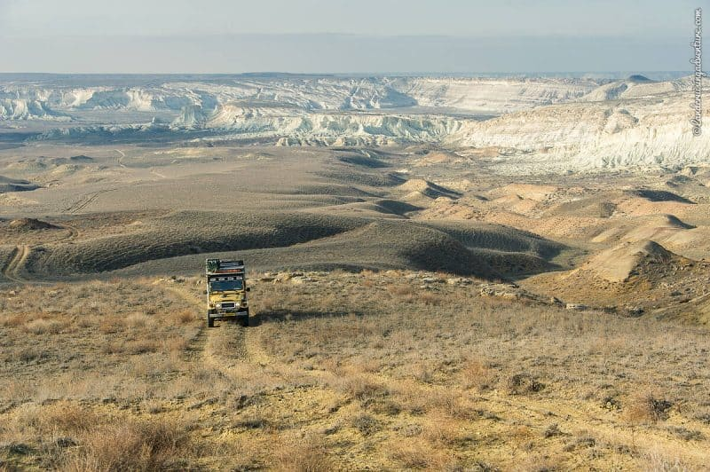 An adventurous road trip through the Mangystau region of Kazakhstan with limestone rock formations and unpaved paths.